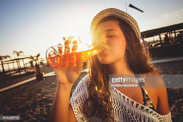 Girl drinking beer at the beach
