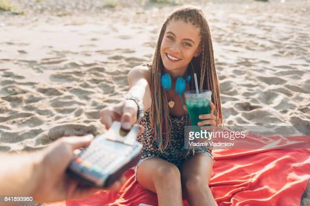 Chica bebiendo cocktail y con tarjeta de crédito para pago sin contacto