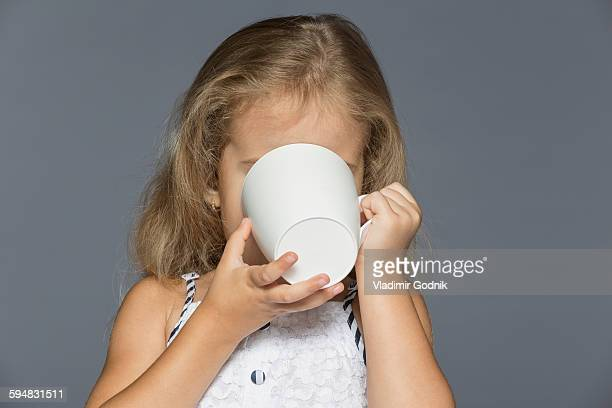 Girl drinking coffee against gray background