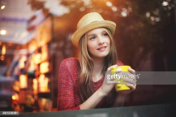 Girl drinking coffee in cafe near window