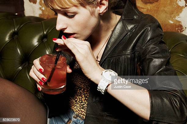 Girl drinking drink with a straw in a sofa