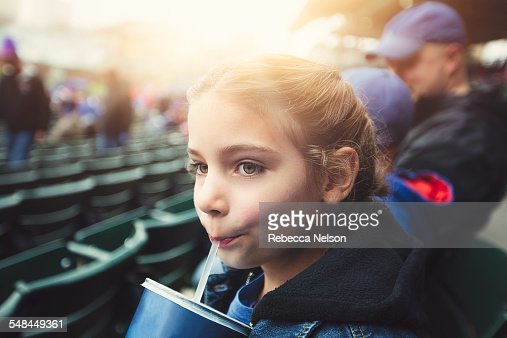 girl drinking from a straw at baseball game