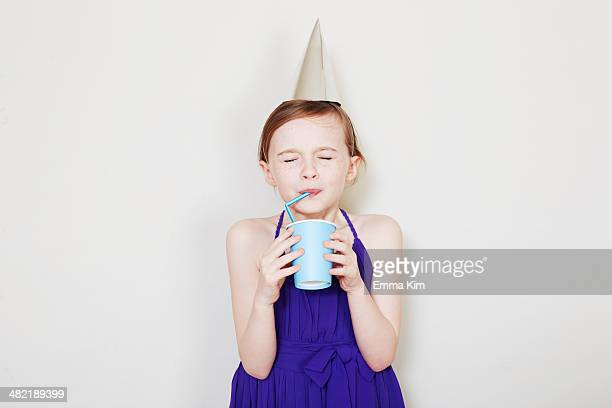 Girl drinking from plastic cup with straw