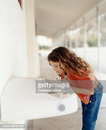 Girl (5-7) drinking from water fountain in school hallway : Stock Photo