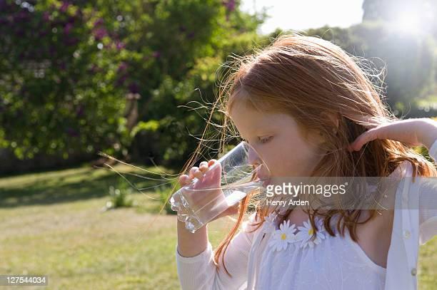 Girl drinking glass of water in backyard