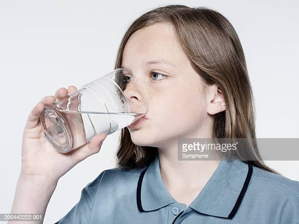 Girl (10-12) drinking glass of water