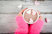Girl drinking hot chocolate with marshmallows in the shape of hearts, Valentine's Day celebration, hands in the picture, top view, copy space