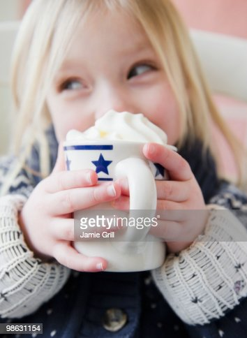 Girl drinking hot chocolate with whipped cream : Stock Photo