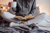 Girl holding cup of hot tea and reading in bed. Around her in bad earphones, book, smart phone. Decorative lights in background.