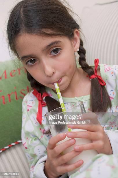 Girl drinking milk through straw