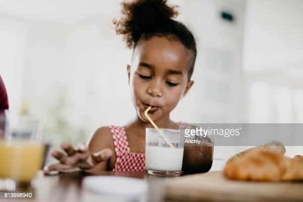 Mädchen trinken Milchshake mit einem Strohhalm