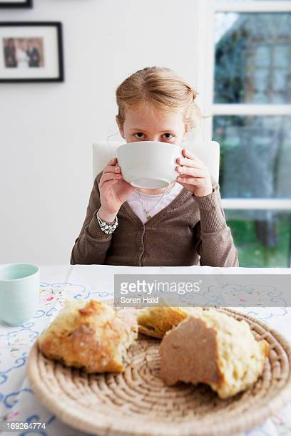 Girl drinking soup from bowl at table