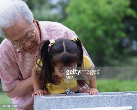 A girl drinking tap water in a park : Stock Photo