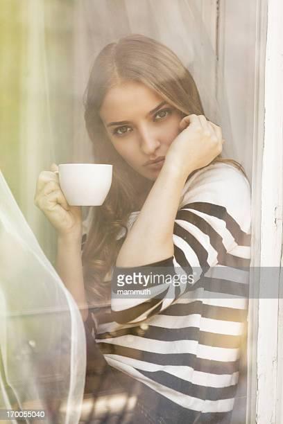 Ragazza di bere tè o caffè nella finestra