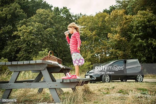 Girl drinking water at a picnic