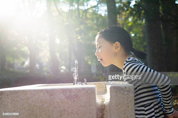 Girl drinking water from public water fountain