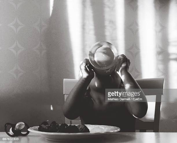 Girl Drinking While Sitting At Table Against Curtain
