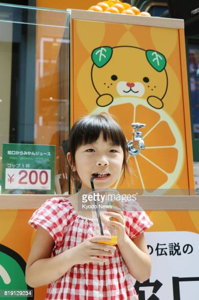 A girl drinks orange juice in front of the 'mikan jaguchi' at newlyopened Orange Bar at Matsuyama airport in the western Japan prefecture of Ehime on...