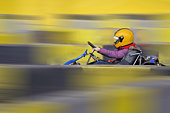 Girl (9) driving a go-cart on a race track