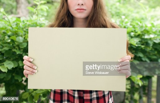 Girl early 20's holding blank sign expressionless  : Bildbanksbilder