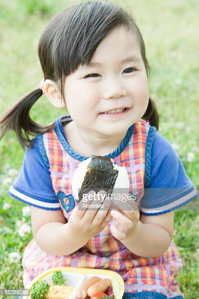 A girl eating a rice ball in a field