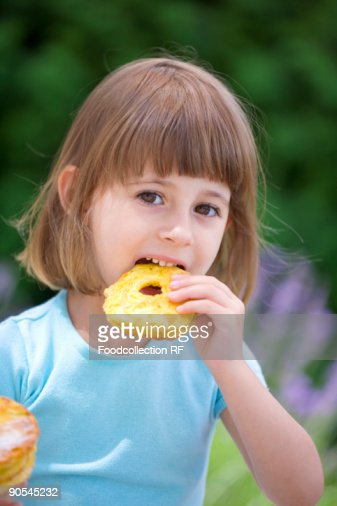 Girl (4-5) eating an apple fritter, close up : Stock Photo