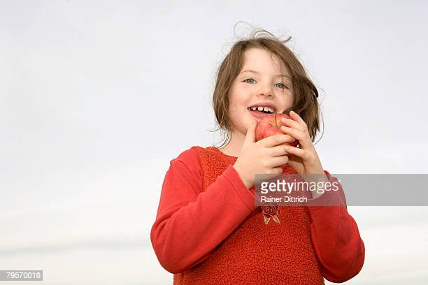 'Girl (7-9) eating apple, close-up'