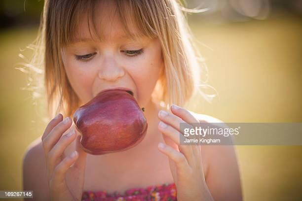 Girl eating apple outdoors