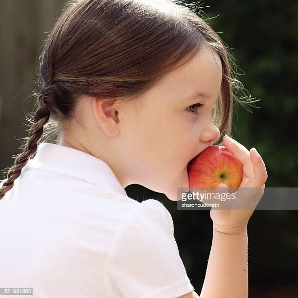 Girl (4-5) eating apple