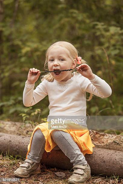 Girl eating blueberries in the forrest.