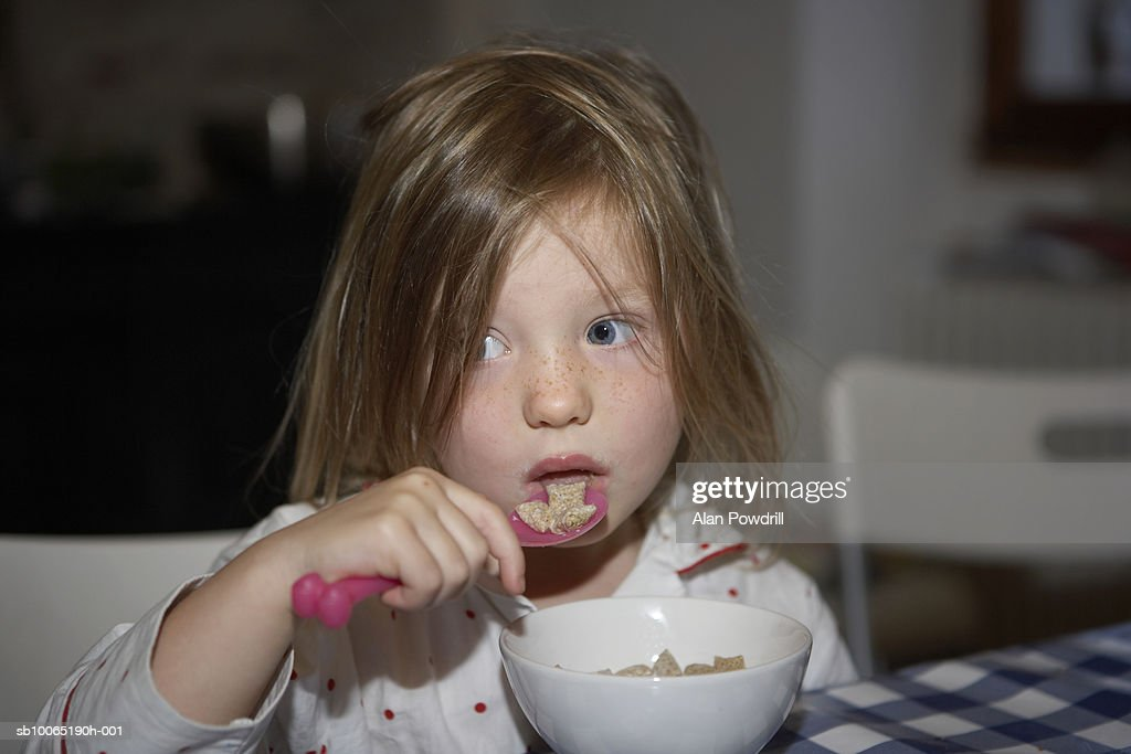 Girl (3-4 years) eating bowl of cereal, close up : Stock Photo