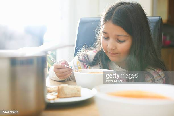 Girl eating bowl of soup in kitchen