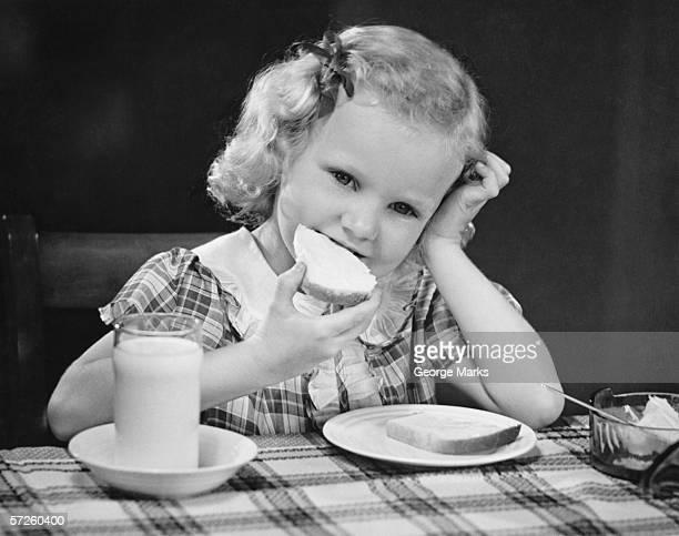 Girl (6-7) eating breakfast, resting head on hand , (B&W)