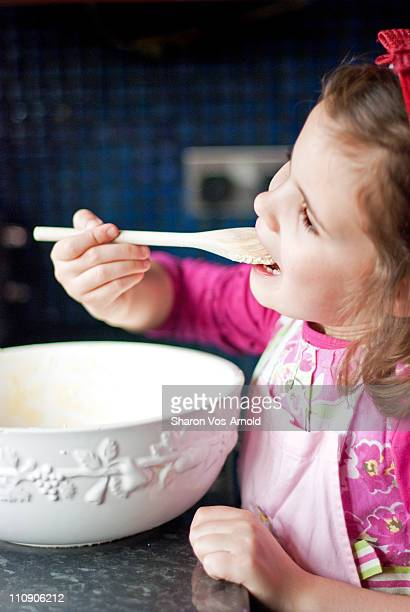 Girl eating cake mix off a wooden spoon (2)