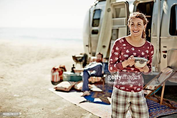 A girl eating cereal outside a camper by the beach