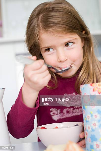Girl eating cereals and fruit