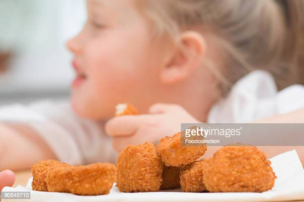 Girl (4-5) eating chicken nuggets, close up