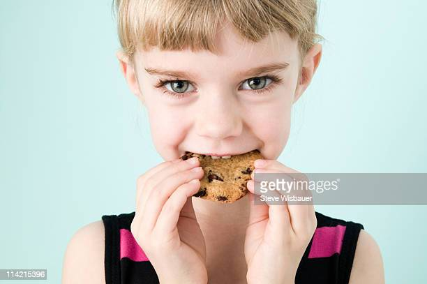 Girl (3-5) eating chocolate chip cookie