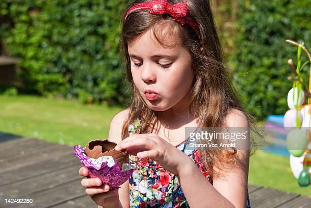 Girl eating chocolate Easter egg in garden