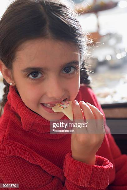 Girl (4-5) eating Christmas biscuit, close up, portrait