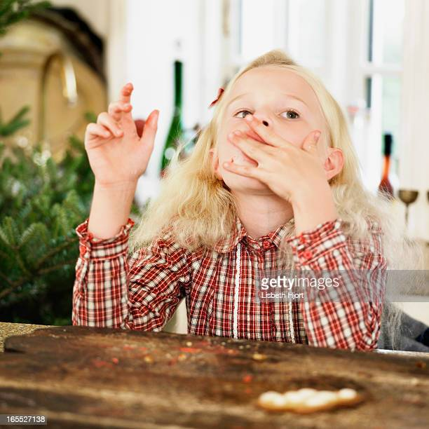 Girl eating Christmas cookies in kitchen