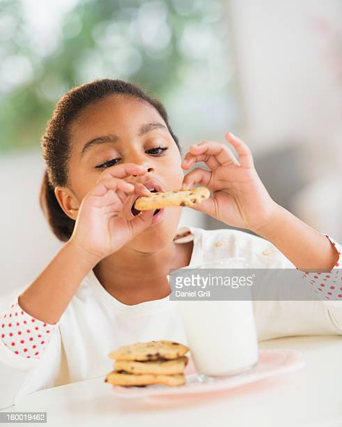 Girl (6-7) eating cookie