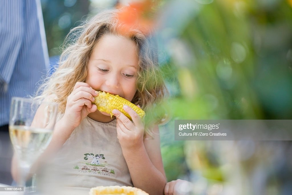 Girl eating corn at table outdoors : Stock Photo