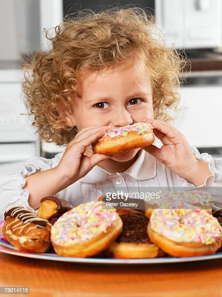 Girl (2-3) eating doughnut, close-up