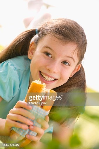 Girl eating fish and salad sandwich at picnic