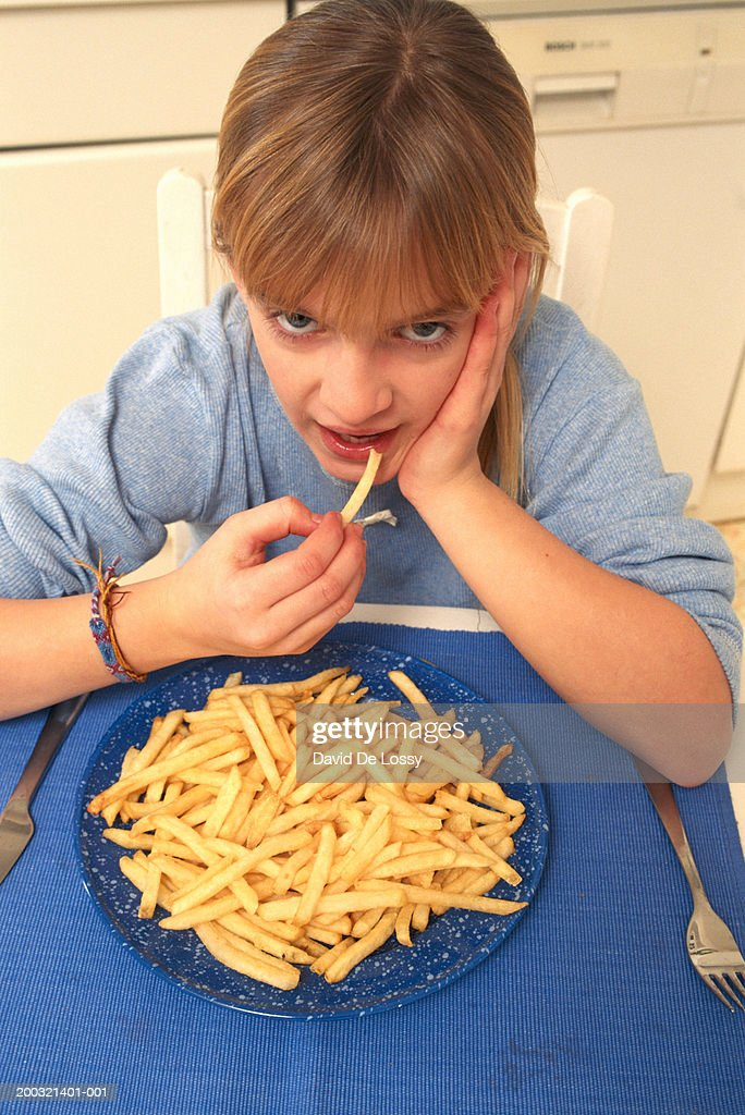 Girl (6-7) eating French fries, elevated view, portrait : Stock Photo