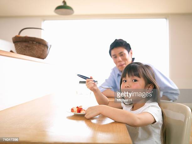 Girl (6-7) eating fruit in kitchen, father in background