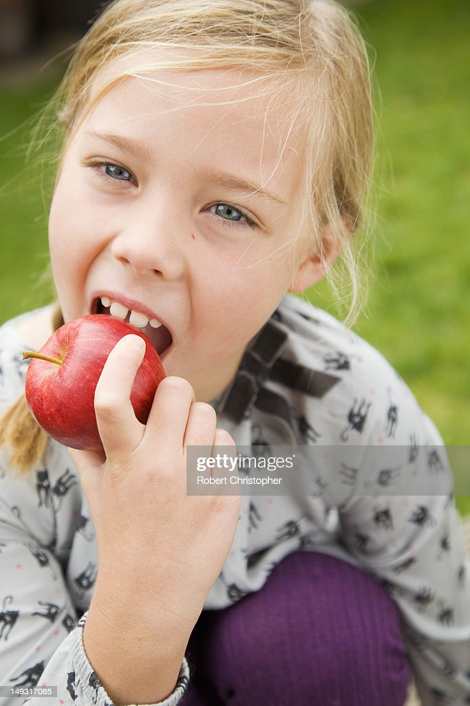 Girl eating fruit outdoors : Stock Photo