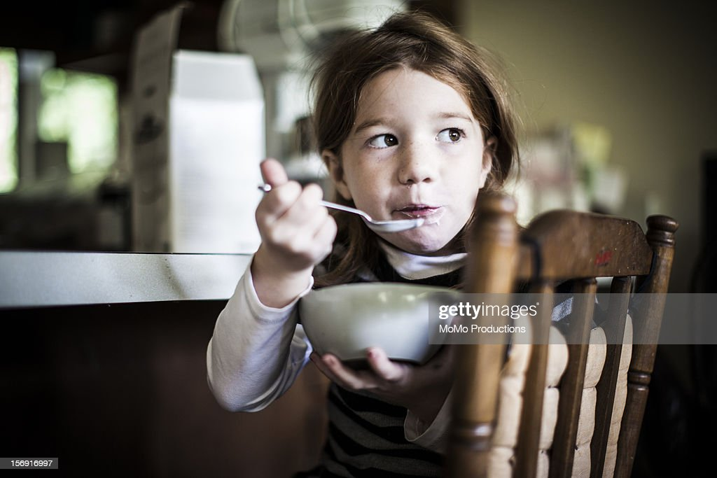Girl (6yrs) eating homemade yogurt from bowl : Stock Photo