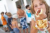 Girl (8-10) eating hotdog, children (6-12) queuing at vendor's window